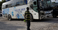 Мужчина смотрит на автобус, въехавший в толпу людей, припаркован в полицейском участке Гонайвса, Гаити. Архивное фото