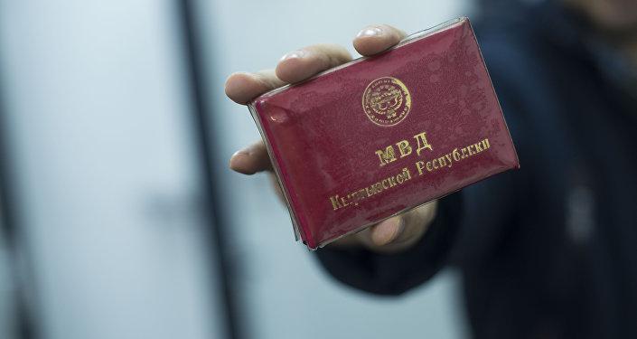 Мужчина показывает корочку сотрудника МВД КР. Архивное фото