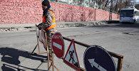 Сотрудник муниципальной службы ставит знак на дорогу запрещающий въезд на полосу
