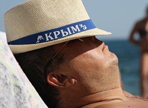 Мужчина отдыхающий на плаже в Крыму. Архивное фото