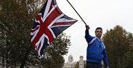 Мужчина машет флагом Великобритании стоя на автомобиле. Архивное фото