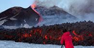 Турист стоит перед вулканом Этна, самым высоким и самым активным вулканом в Европе во время извержения на южном острове Сицилия, Италия. Архивное фото