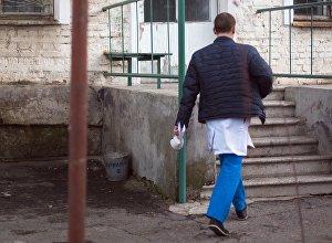 Сотрудник больницы перед входом в стационарное здание. Архивное фото