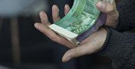 Мужчина держит деньги и обручальное кольцо. Архивное фото
