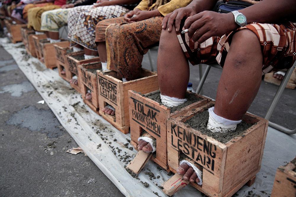 Индонезиянын Жакарта шаарында цемент заводдун курулушуна нааразы болгон фермерлер каршылыгын билдирүү үчүн буттарына цемент куюп салышты