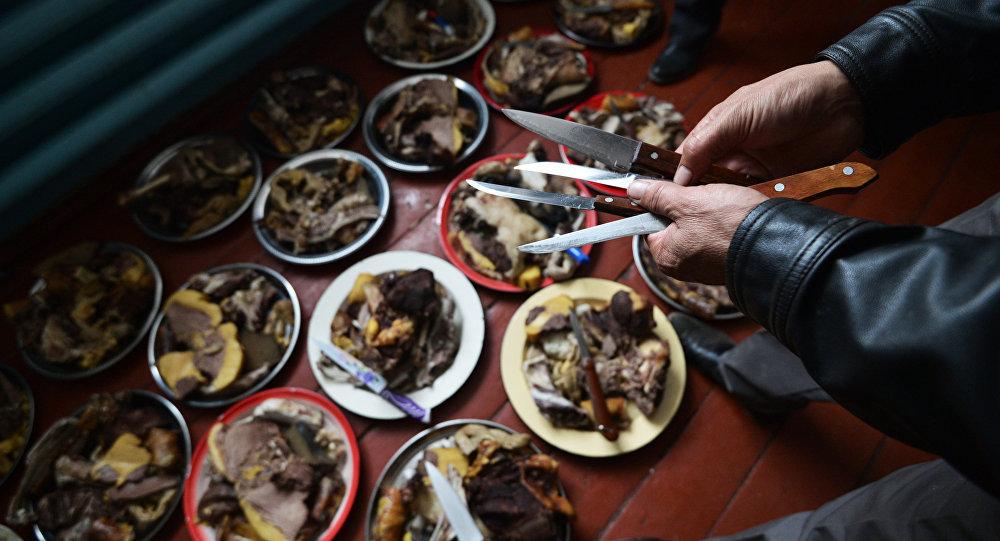 Мужчина готовят мясо во время празднования свадьбы. Архивное фото