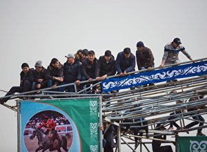 Зрители, которые забрались на арку городского ипподрома Ак-Кула, во время конноспортивных игр в рамках празднования Нооруза