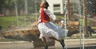 Девочка играет в фонтане на центральной площади. Архивное фото