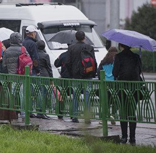 Люди на остановке во время дождя в Бишкеке. Архивное фото