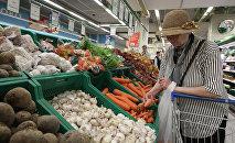 Женщина выбирает овощи в торговом зале супермаркете. Архивное фото