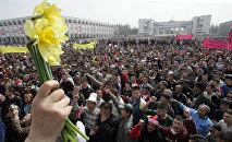 Женщина с цветами во время митинга оппозиции на центральной площади Бишкека, 24 марта 2005 года