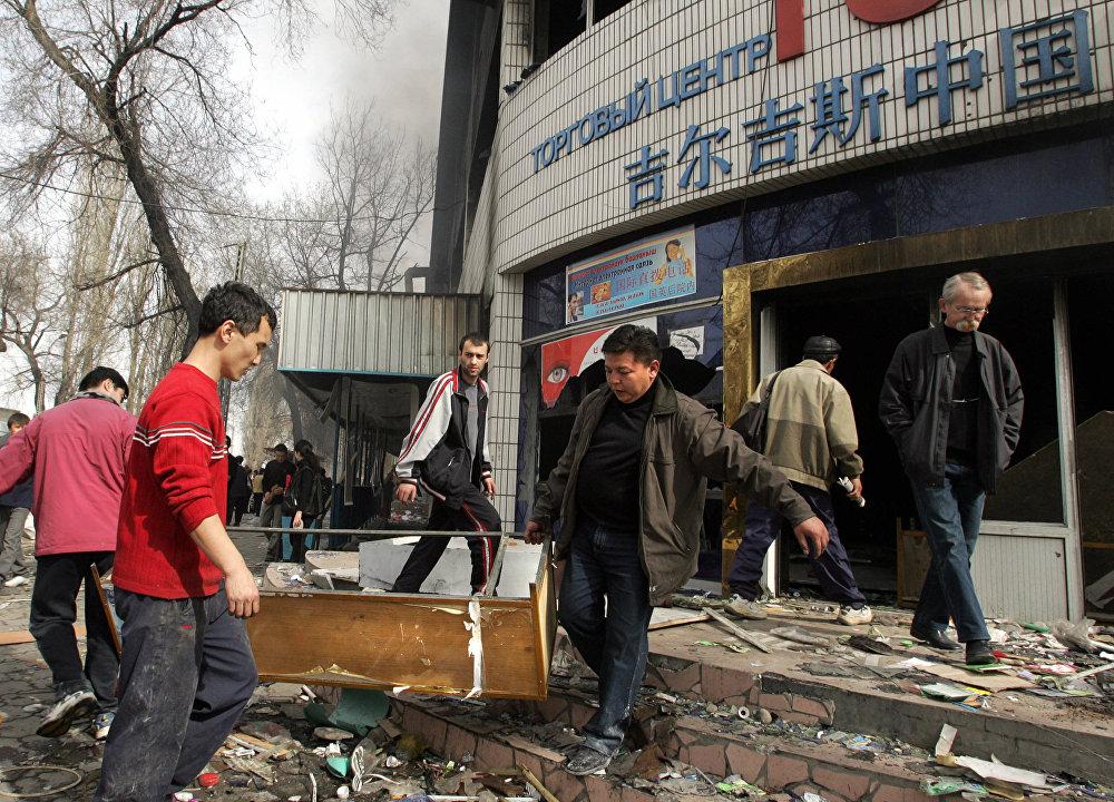 Мародерлор өрттөп жиберген кытай соода борборунда калган эмеректи сыртка алып чыгып жаткандар. 2005-жылдын 25-марты