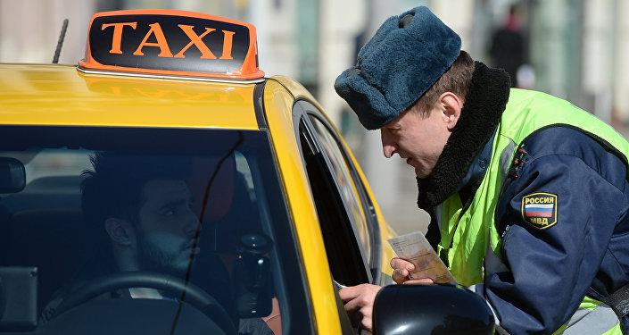 Сотрудник ГИБДД проверяет документы у водителя в рамках рейда против нелегальных таксистов в Москве. Архивное фото