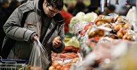 Покупатель выбирает продукты в супермаркете. Архивное фото