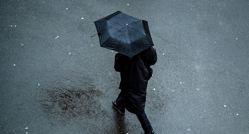 Прохожий с зонтом во время дождя. Архивное фото