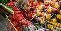 Девочка в гипермаркете на прилавке с овощами. Архивное фото