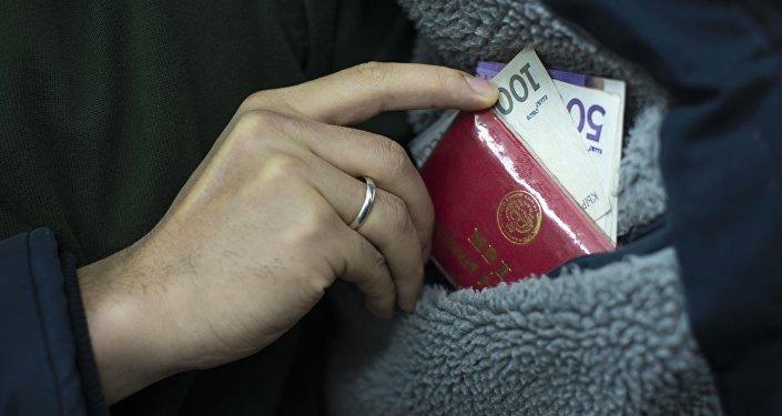 Мужчина кладет удостоверение сотрудника МВД КР с деньгами в карман. Архивное фото