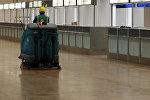 Пол жууган машинаны башкарып бараткан аэропорт кызматкери. Архив