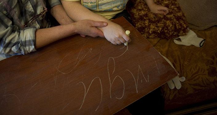 Женщина с ребенком на занятиях по аутизму. Архивное фото