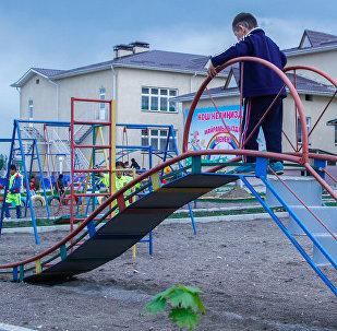 Мальчик играет на горке в детском саду. Архивное фото