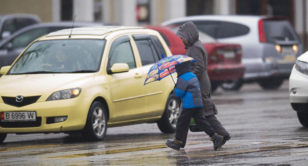 Женщина с ребенком переходят улицу во время дождя в Бишкеке. Архивное фото