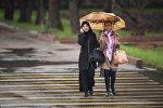 Жители Бишкека с зонтом во время дождливой погоды. Архивное фото