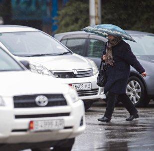 Женщина с зонтом на одном из улиц Бишкека. Архивное фото