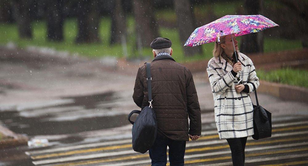 Горожане во время дождливой погоды на одной из улиц Бишкека. Архивное фото