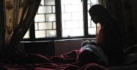 Женщина сидит с ребенком у окна. Архивное фото