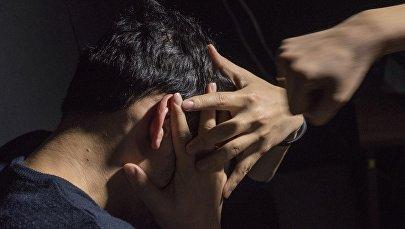 Мужчина закрывает лицо от удара. Архивное фото