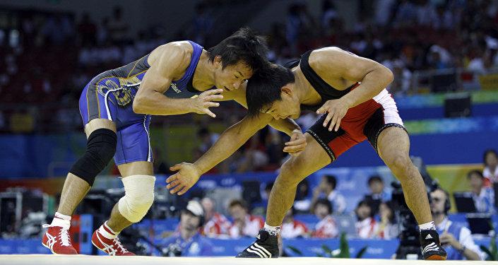 Японский борец Кеничи Юмотой и спортсмен из Кыргызстана Базар Базаргуруев (справа) во время вольной борьбы на Олимпийских играх в Пекине. 19 августа 2008 года