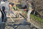 Выпускники местной школы во время ямочного ремонта сельской дороги в Лейлекском районе Баткенской области