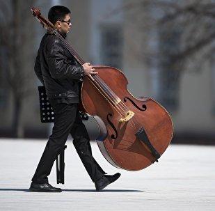 Контрабас ташыган музыкант. Архивдик сүрөт