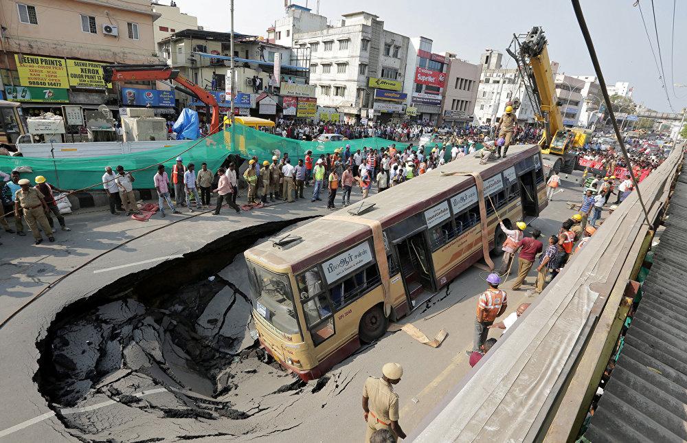 Индияда чоң магистралдардын биринде асфальт чөгүп кетип, оңбогондой чуңкурду пайда кылган. Ага автобус жана жеңил автоунаа түшүп кетип, бир нече киши жабыркады