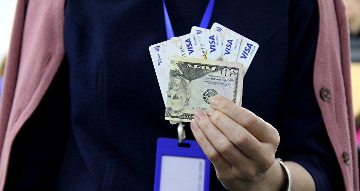 Банковские карты и долларовая купюра в руках человека. Архивное фото