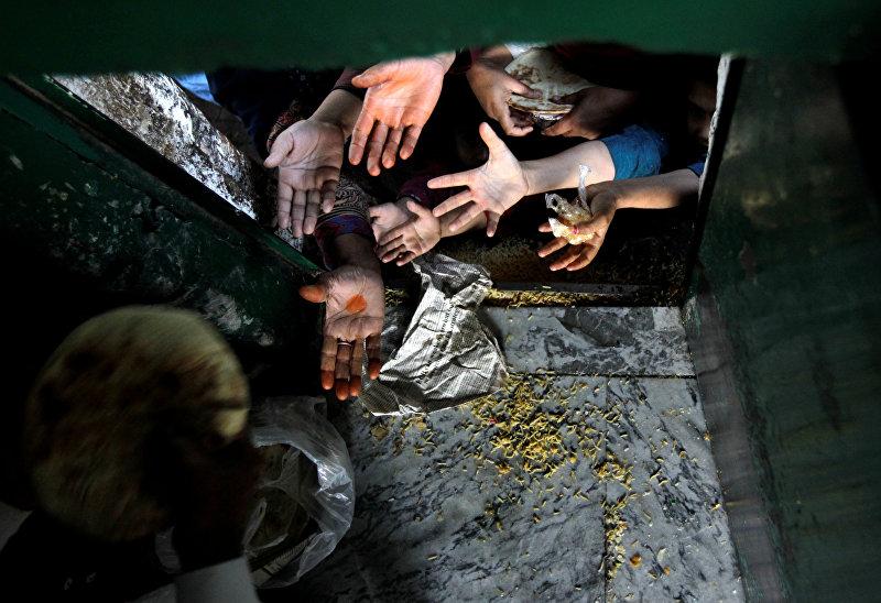 Женщины и дети в центре раздачи бесплатного питания в храме в Исламабаде. Пакистан