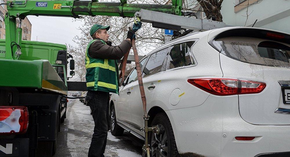 Сотрудник эвакуирует неправильно припаркованный автомобиль. Архивное фото