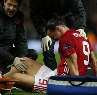 Футболист ФК Манчестер Юнайтед Златан Ибрагимович получает медицинскую помощь после получения травмы в матче Манчестер Юнайтед с Андерлехтом
