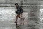 Житель идет по улице во время дождя. Архивное фото