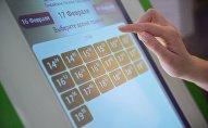 Пациентка выбирает дату и время приема к врачу в терминале электронной очереди в городской поликлинике в России. Архивное фото