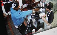 Клиент делает заказ, после чего достает из кармана пистолет и направляет дуло в лицо сотруднику заведения. Фото с сайта Youtube