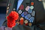 Ветеран войны с гвоздикой в руке. Архивное фото