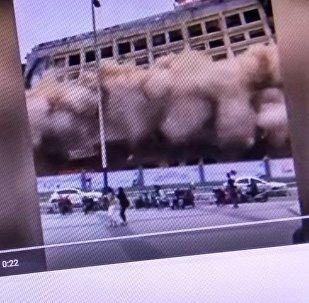 Youtube видеохостингинин Demolition Sends Pedestrians Fleeing каналынан тартылып алынган кадр.  Кытайдын Чжанчжоу шаарындагы 12 кабаттуу имаратты уратып бузу