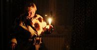 Жительница города со свечами в квартире. Архивное фото
