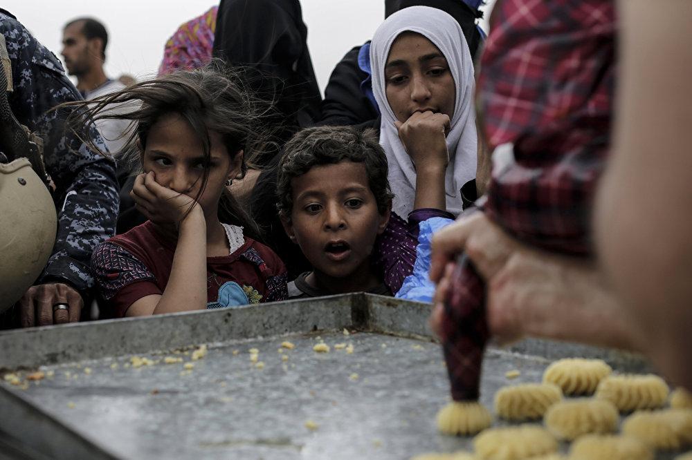 Ирак. Мосул шаарынын батыш тарабы. Согуш жашоосуна так салган балдар. Тамак-аш бөлүштүргөн жерде бышырылып жаткан таттууну карап турган учуру