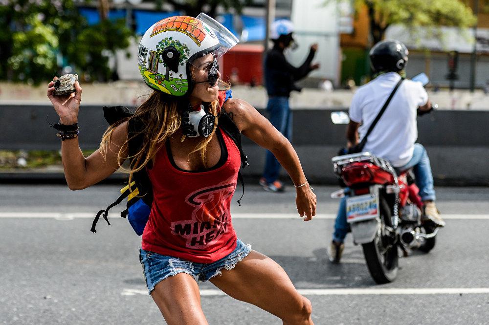 Каракастагы (Венесуэла) нааразылык акциясына чыккан аял полиция менен кагылышуу учурунда. Колунда таш, башында каска. Массалык митинг 4-апрелден бери тынчыбай келет. Баарына күнөлүү баягы эле саясат