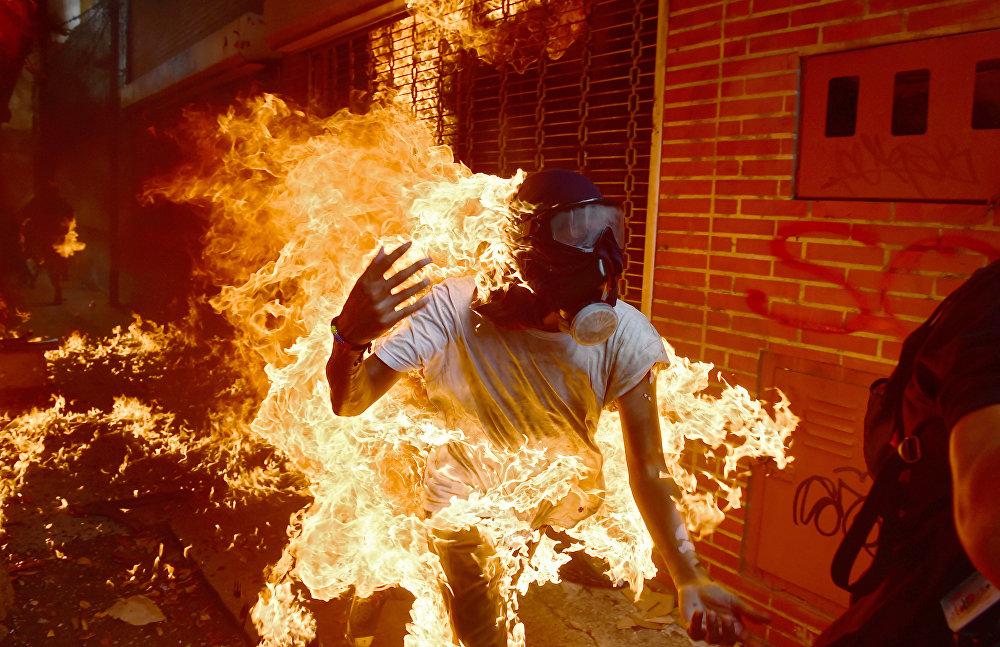 Каракас (Венесуэла). Демонстранттар менен кагылышууда полиция минип жүргөн мотоциклдин бензин куйган багы жарылып кеткен учуру