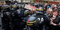Французская полиция окружила демонстрантов, которые держат плакат с надписью Государство не компания после президентских выборов в Париже. Франция, 8 мая 2017 года