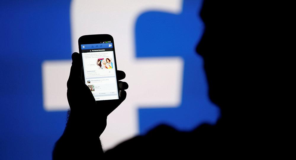 Человек смотрит на мобильный телефон с логотипом Facebook. Архивное фото