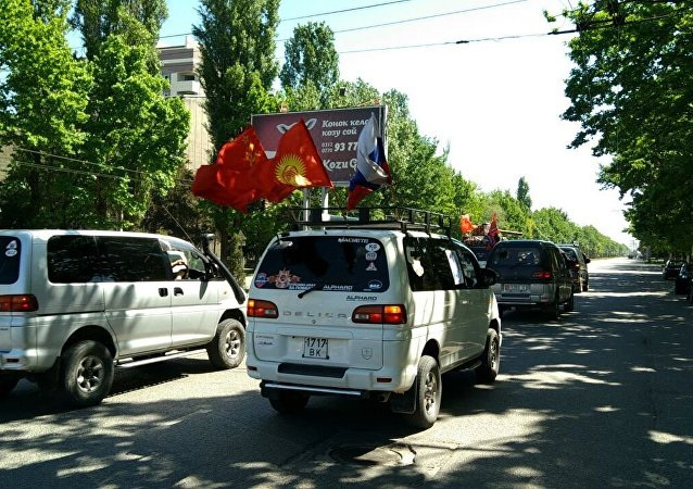 Около 80 автомобилей разных марок, украшенных георгиевскими ленточками и прочими символами Дня Победы движутся по улице Дооронбека Садырбаева (Баха).